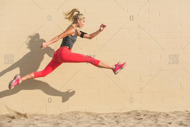 Female athlete leaping over sand