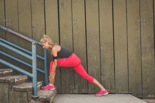 Female athlete stretching legs on stairs