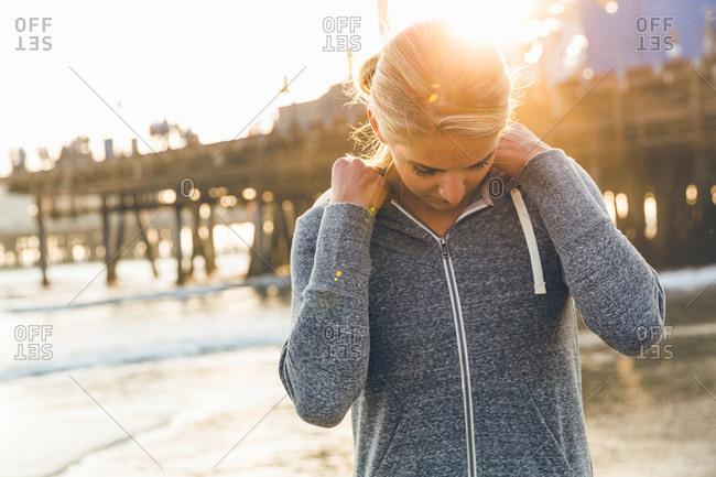 Female athlete adjusting hood on beach