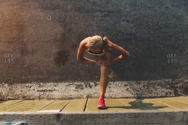 Female athlete stretching against a wall