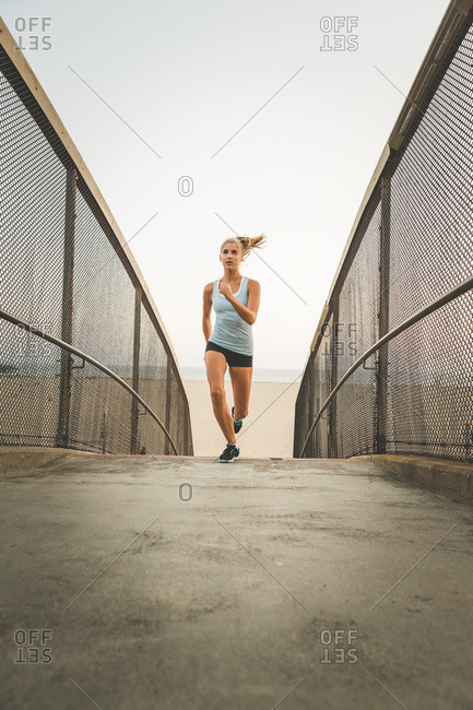 Female jogger running on footbridge