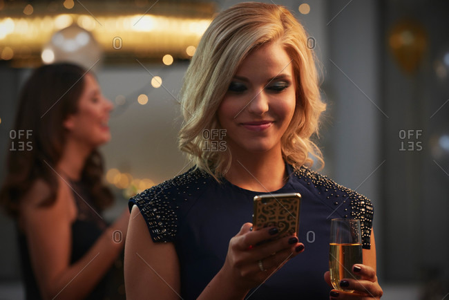 Blonde woman in a blue dress drinking champagne and using smart phone