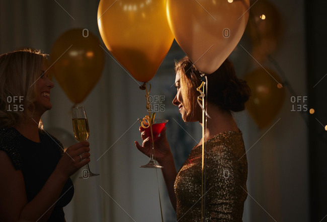 Stylish women interacting over evening cocktails in room with balloons