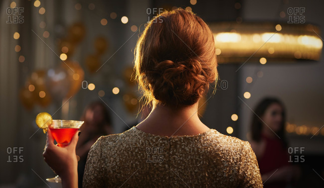 Back view of woman dressed in gold holding red cocktail