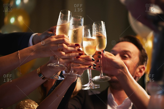 Friends holding up champagne flutes together in a toast at a celebration