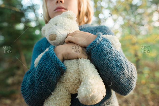 Boy holding teddy bear in countryside