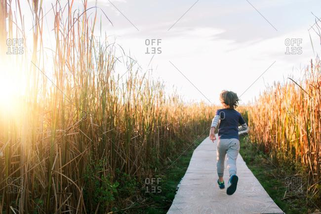 Boy running down rural wood path