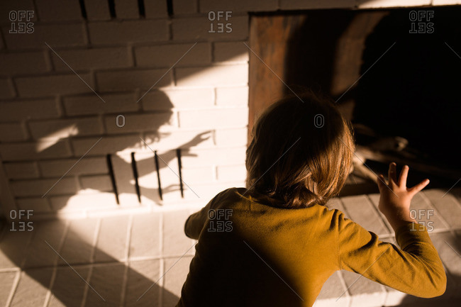 Boy making shadows on a fireplace