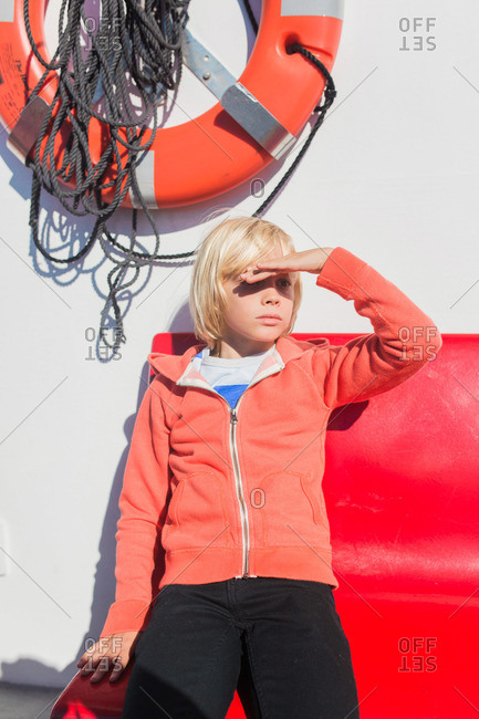 Boy on ferry shielding face from sun