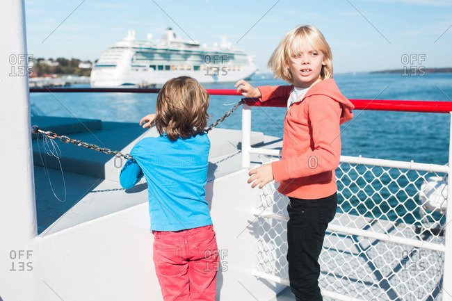Boys looking at ship from ferry