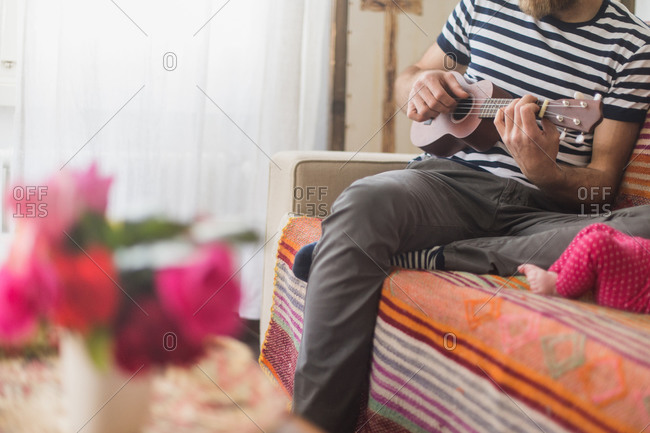 Man on couch playing a ukulele