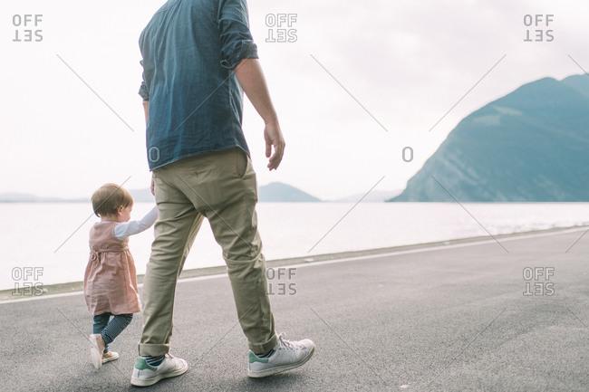 Dad holding girl's hand on coastal road