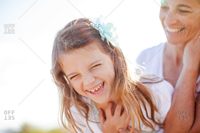 Amused woman watches as her daughter doubles over with laughter
