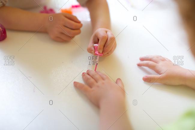 Girl painting sisters fingernails