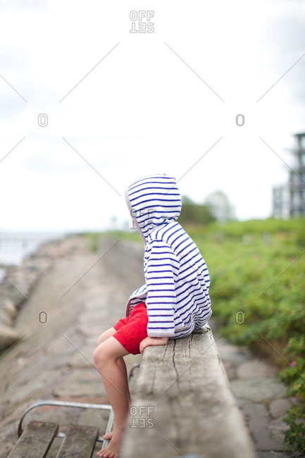 Boy sitting on embankment