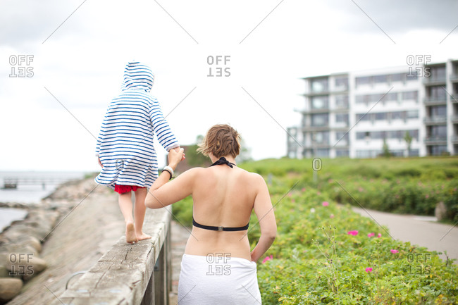 Mother with son walking on embankment