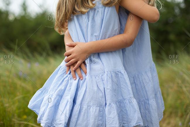 Little girls embracing each other at grass field