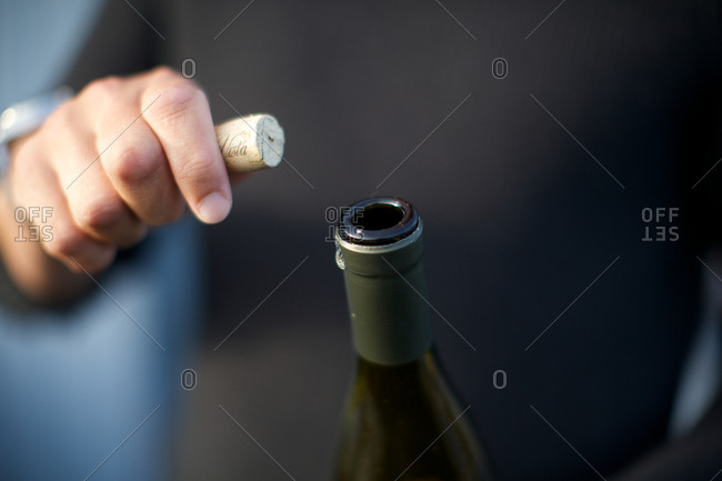 Man holding wine bottle and cork