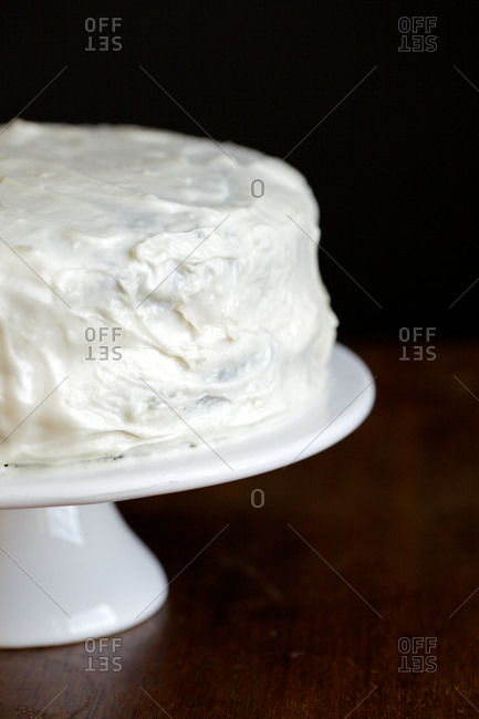 White cake on stand with dark background