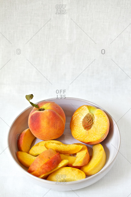 Whole and sliced peaches in bowl