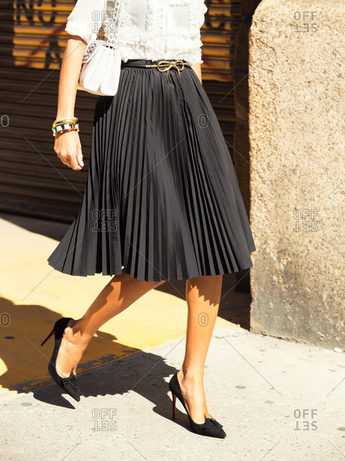 Woman in a black accordion skirt and heels