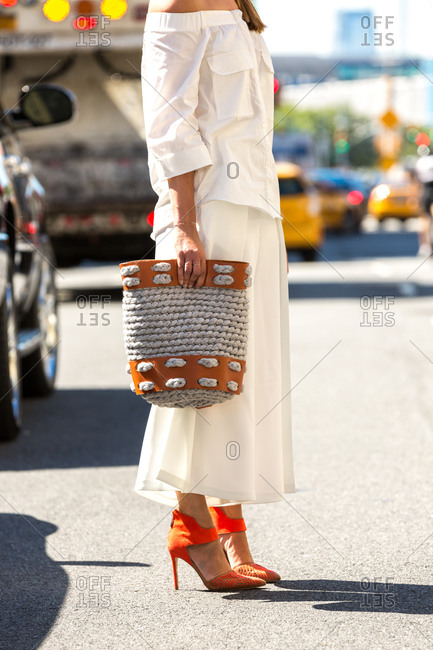 Woman in a white slouchy shirt and skirt standing in a street