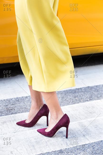 Woman in yellow cropped pants and burgundy high heels