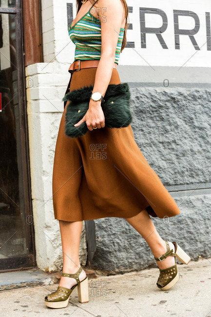 Woman in a mid-calf brown skirt with chunky heels