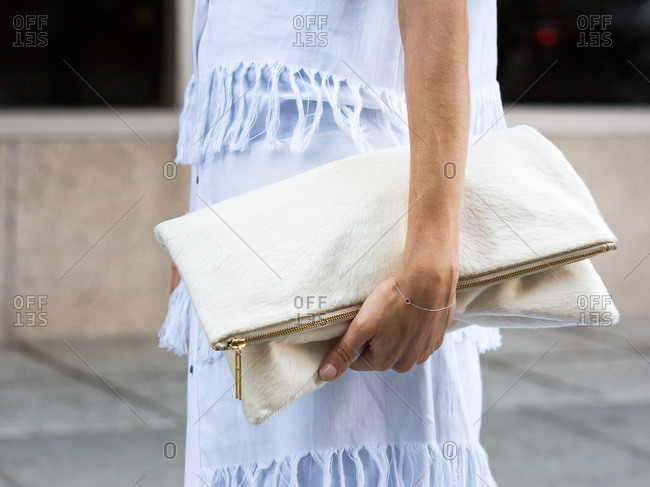 Woman in a fringed outfit holding a linen clutch