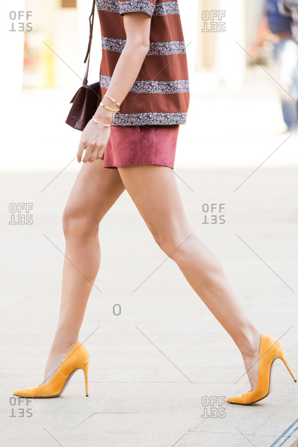 Woman in burgundy shorts and orange high heels