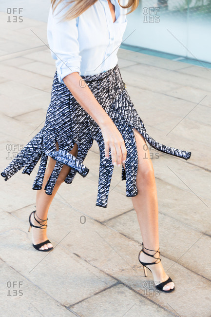 Woman in patterned fringed skirt and heels
