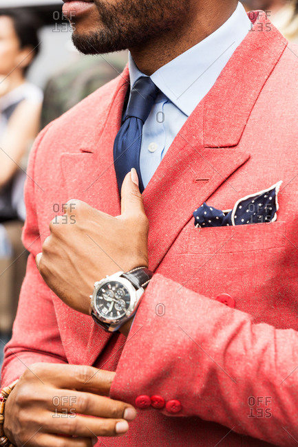 Man in a salmon blazer adjusting his cuff