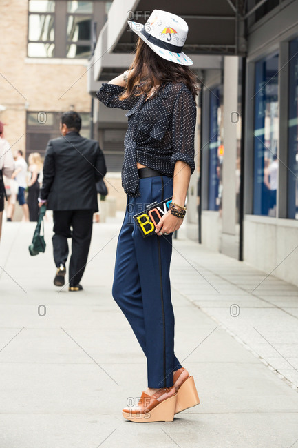 "Woman in a tie-front shirt and wedge shoes holding a clutch that says ""boys"""