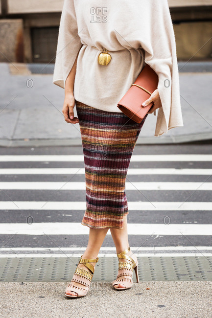 Woman in an oversized sweater and striped knit skirt