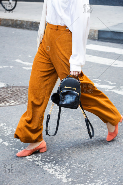 Woman in oversized pants carrying a small leather backpack