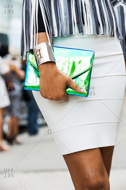 Woman in a white skirt and fringed top with an iridescent clutch purse