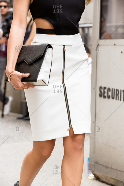 Woman in a zip-front skirt carrying a clutch purse