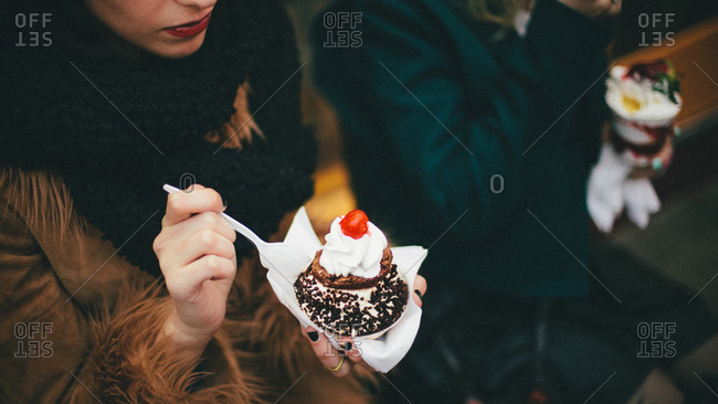 Two women eating ice cream desserts