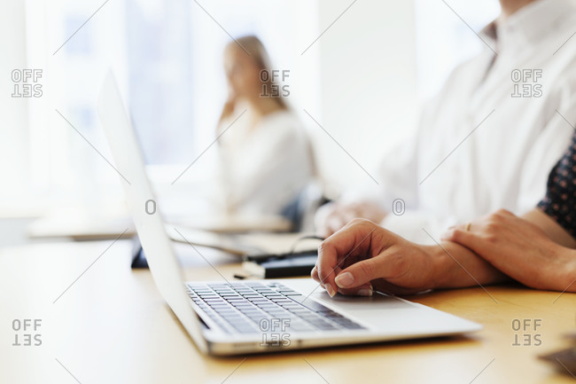 Closeup of women's hands at keyboard with people in background