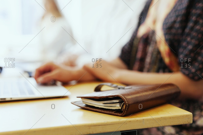 Closeup of woman's planner on table with laptop at office meeting