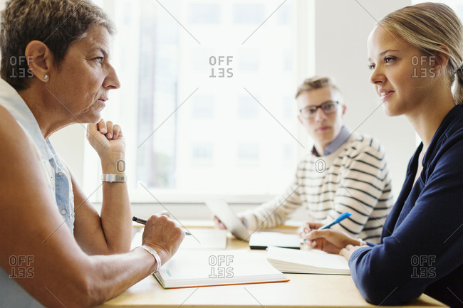 Young woman talking to professor as fellow student listens at table in classroom