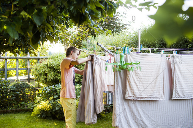 Boy hanging linens on clothesline in garden