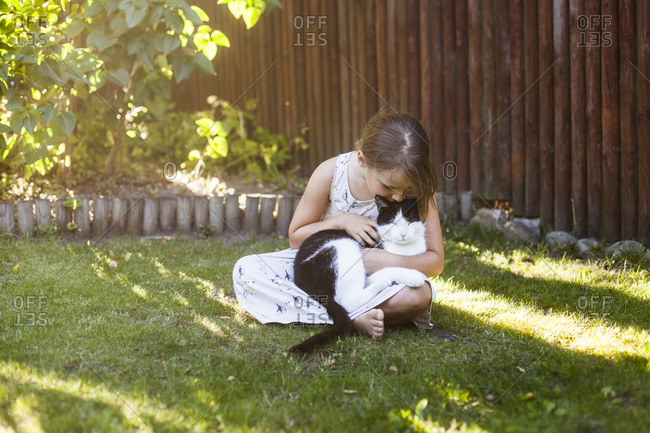 Young girl kisses her cat as she sits on grass in backyard