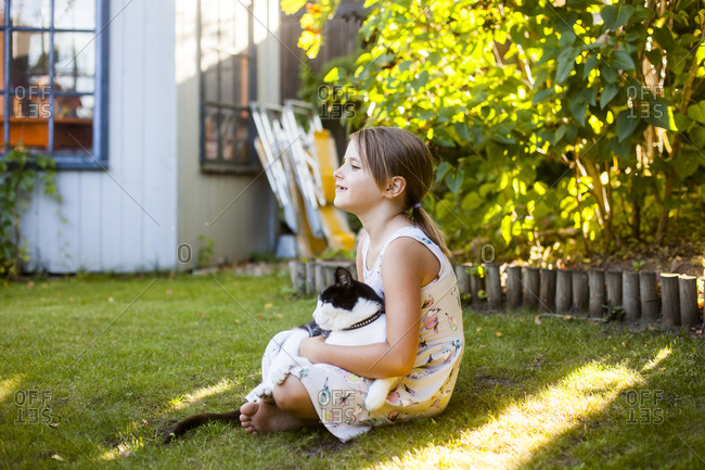 Cat sitting on young girl's lap in garden