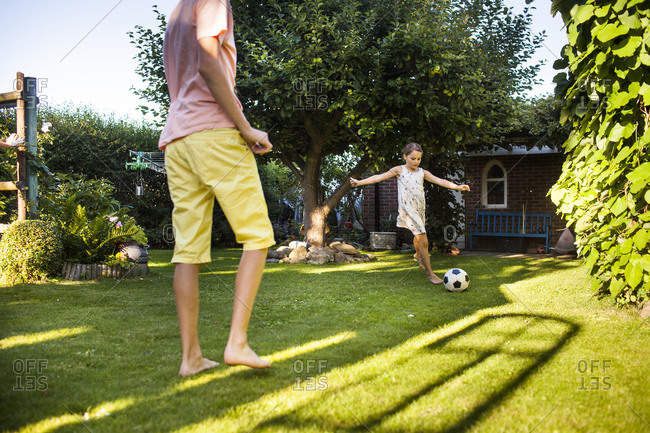 Two siblings kick soccer ball in their beautiful backyard