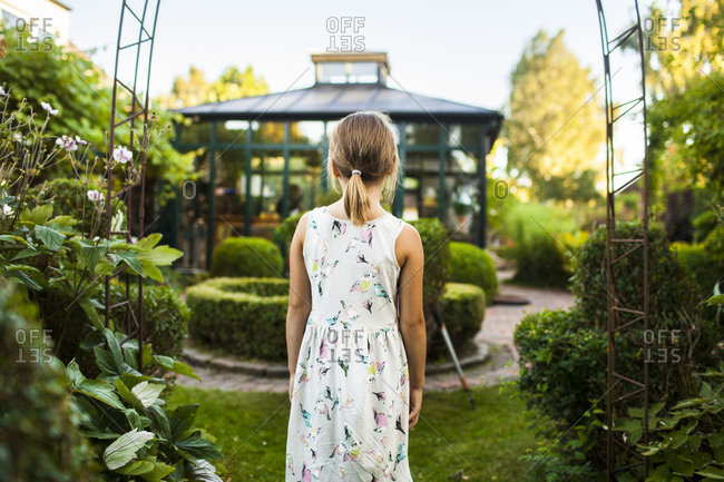 Back view of young girl standing in a luxurious garden with greenhouse