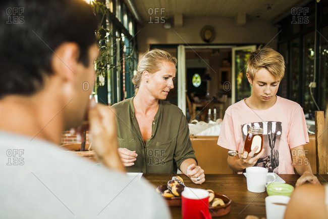 Woman watches son with honey at table set for tea in greenhouse