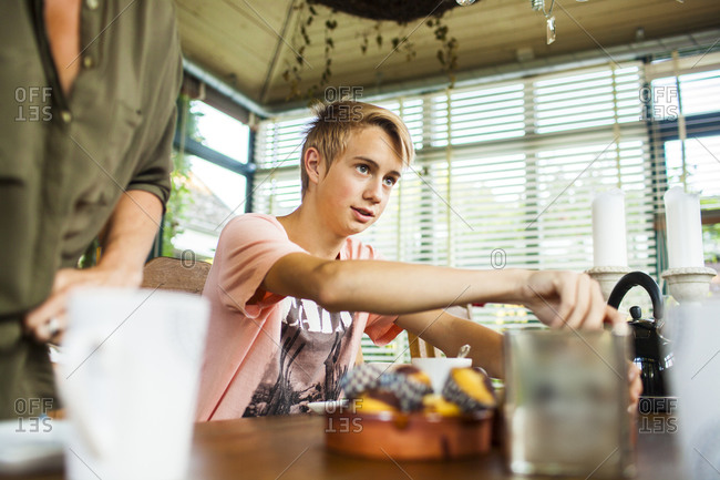 Teen boy sitting at table for tea and snacks