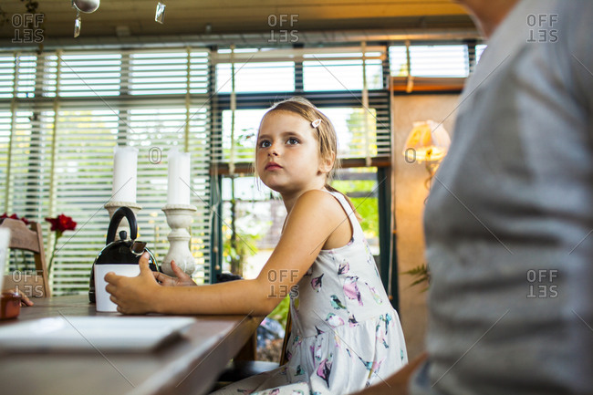 Young girl sitting at table next to tea kettle