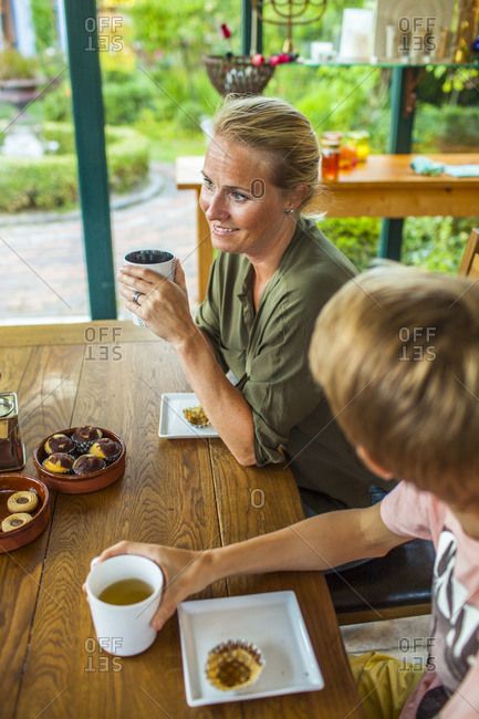 Elevated view of woman having tea and muffins at table with her son